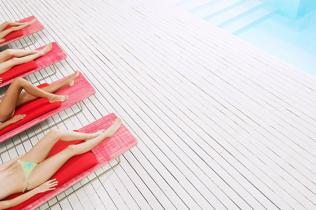 Young Women Sunbathing by pool on deckchairs low section high angle view : Stock Photo