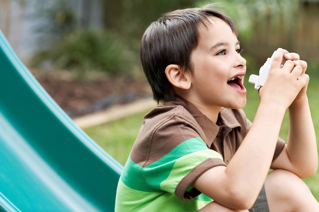 Little boy on slippery slide in park using inhaler : Stock Photo