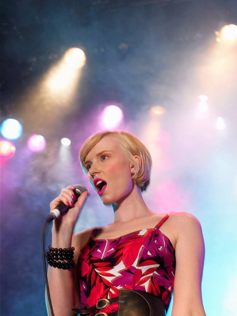 Stock Photo: 1654R-8621 Young Woman Singing in Concert on stage low angle view