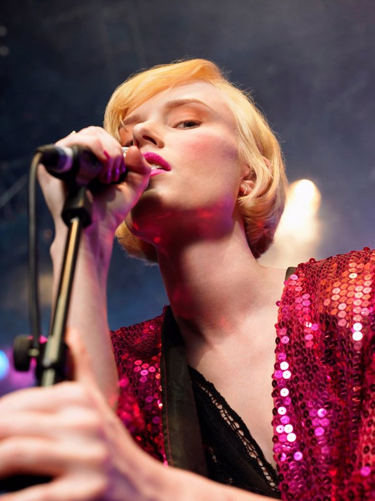 Young Woman Singing in Concert on stage low angle view close up : Stock Photo