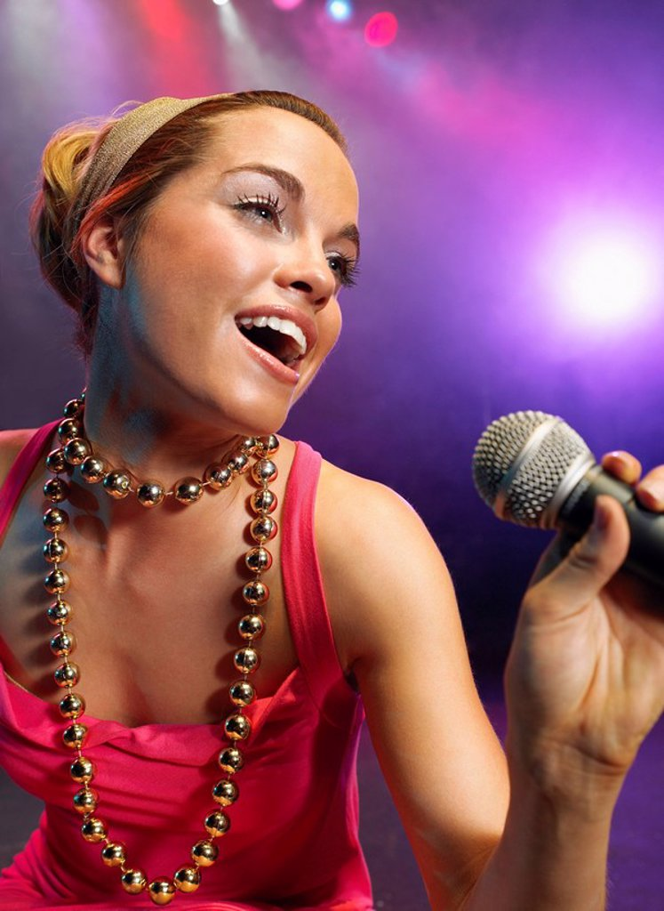 Young Woman Singing on stage in Concert close up low angle view : Stock Photo