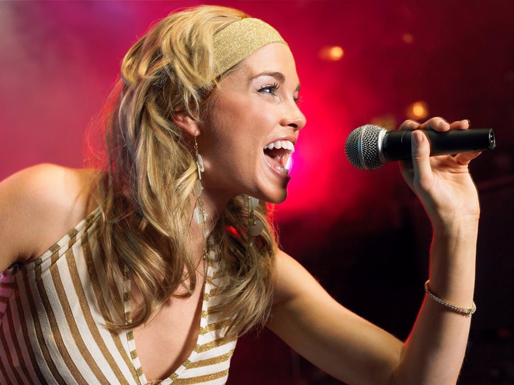 Young Woman Singing on stage in Concert side view : Stock Photo
