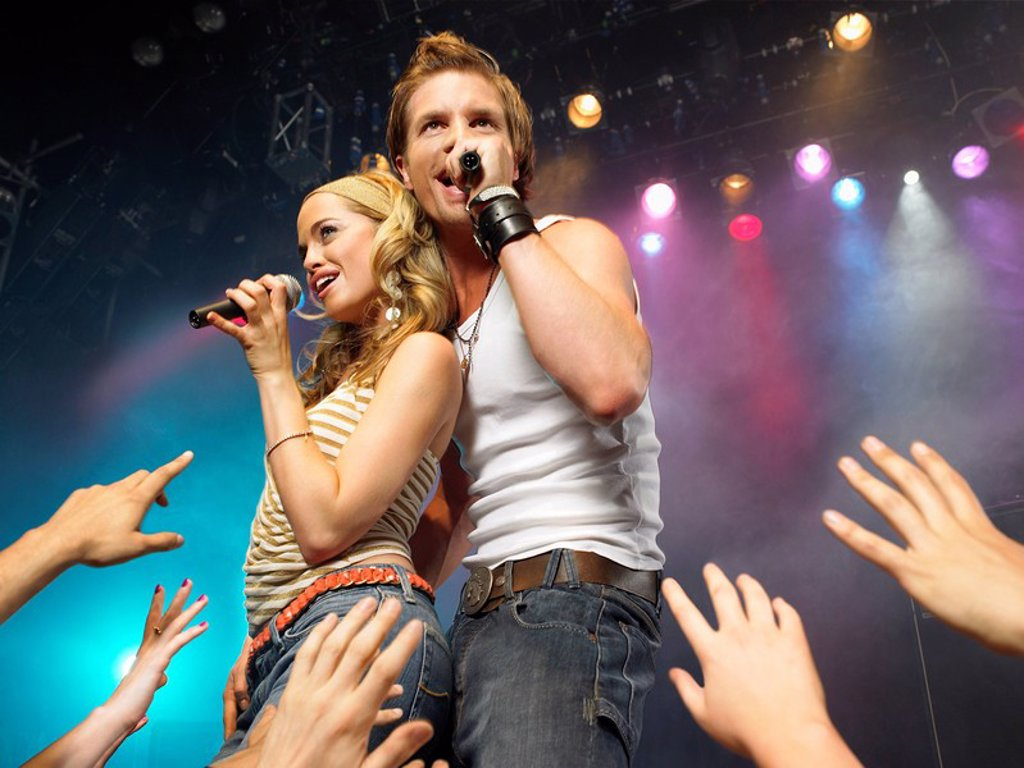 Young man and woman singing on stage in concert in front of adoring fans low angle view : Stock Photo