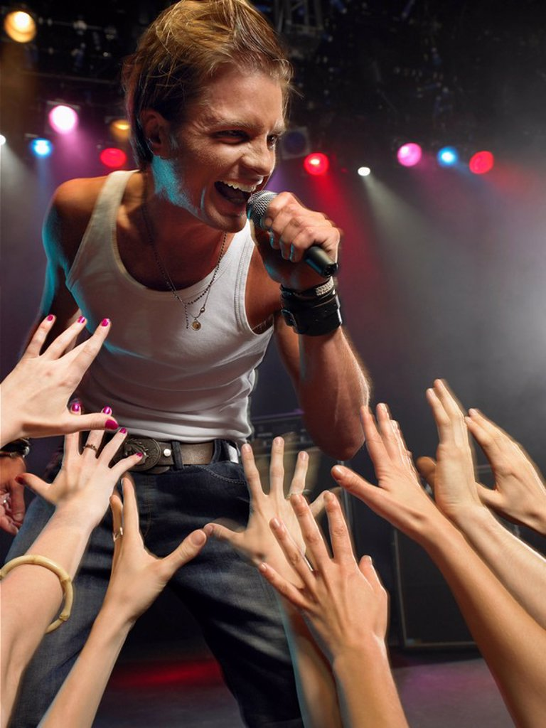Young Man Singing on stage in concert close to adoring fans low angle view : Stock Photo