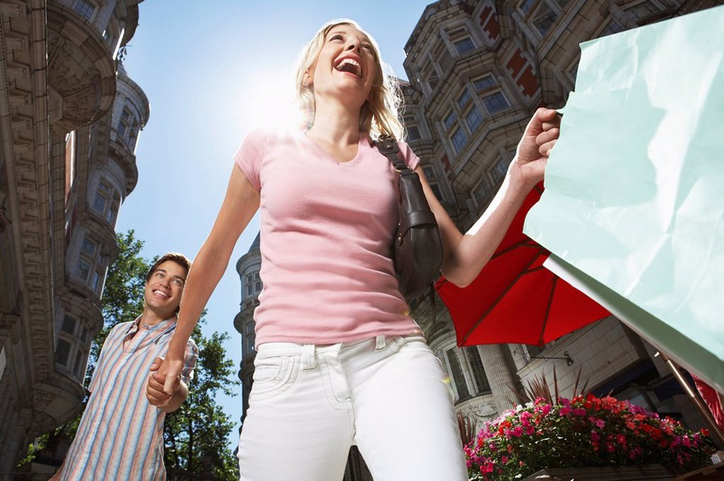 Young couple walking down sity street holding shopping low angle view : Stock Photo