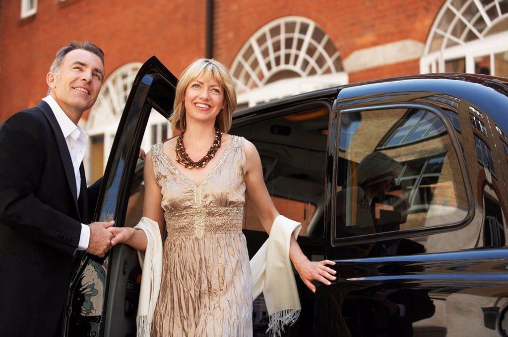 Stock Photo: 1654R-8870 Well dressed couple exiting London taxi