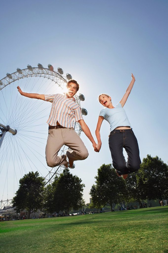 Young couple in park jumping in air in front of London Eye portrait low angle view : Stock Photo