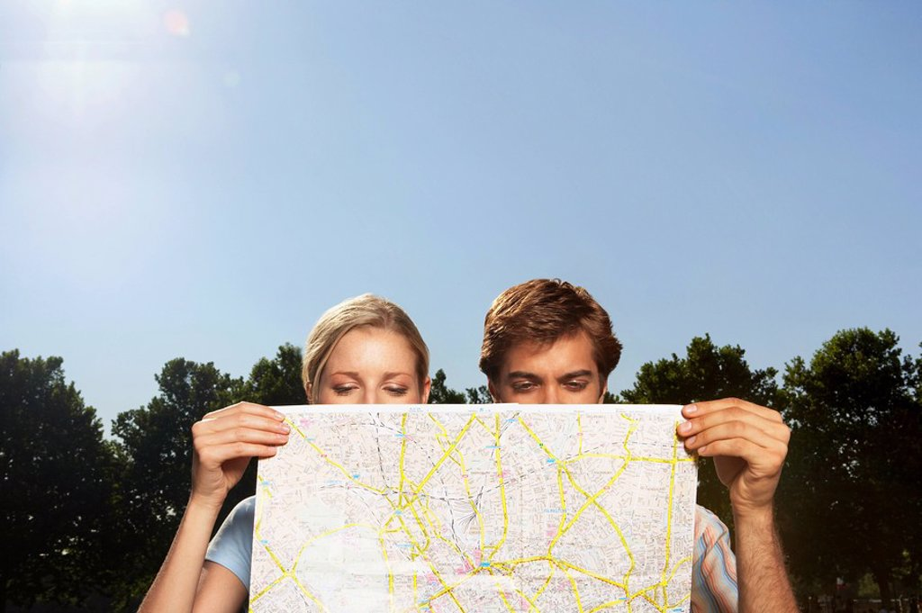 Vacationing couple in park looking at large map : Stock Photo
