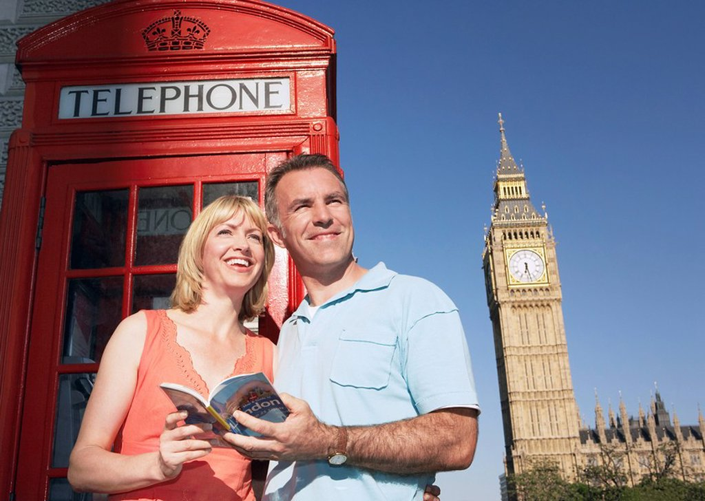 Couple with guidebook standing by London phone booth : Stock Photo