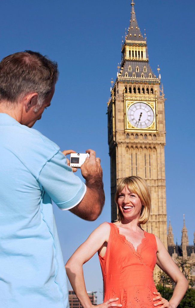 Husband taking photo of wife by Big Ben Tower London England : Stock Photo