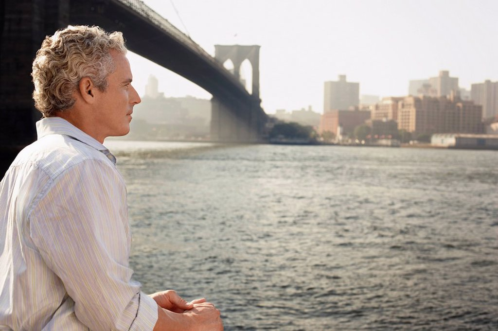 Stock Photo: 1654R-8941 Man looking at river by Brooklyn Bridge