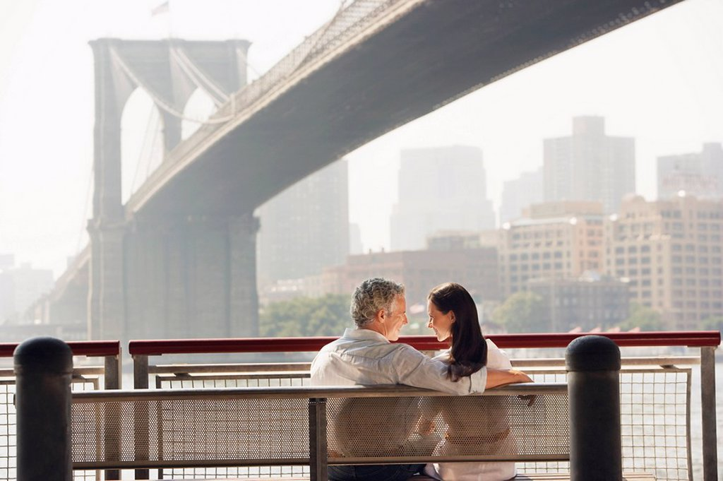 Stock Photo: 1654R-8950 Couple relaxing on bench under Brooklyn Bridge