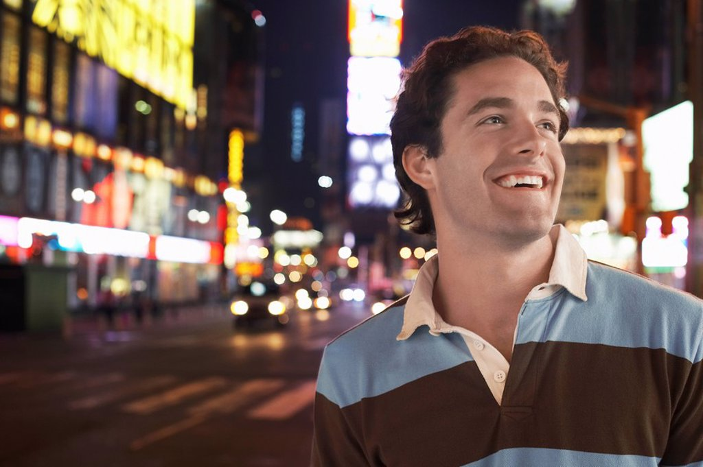 Young man standing in Times Square New York at night : Stock Photo