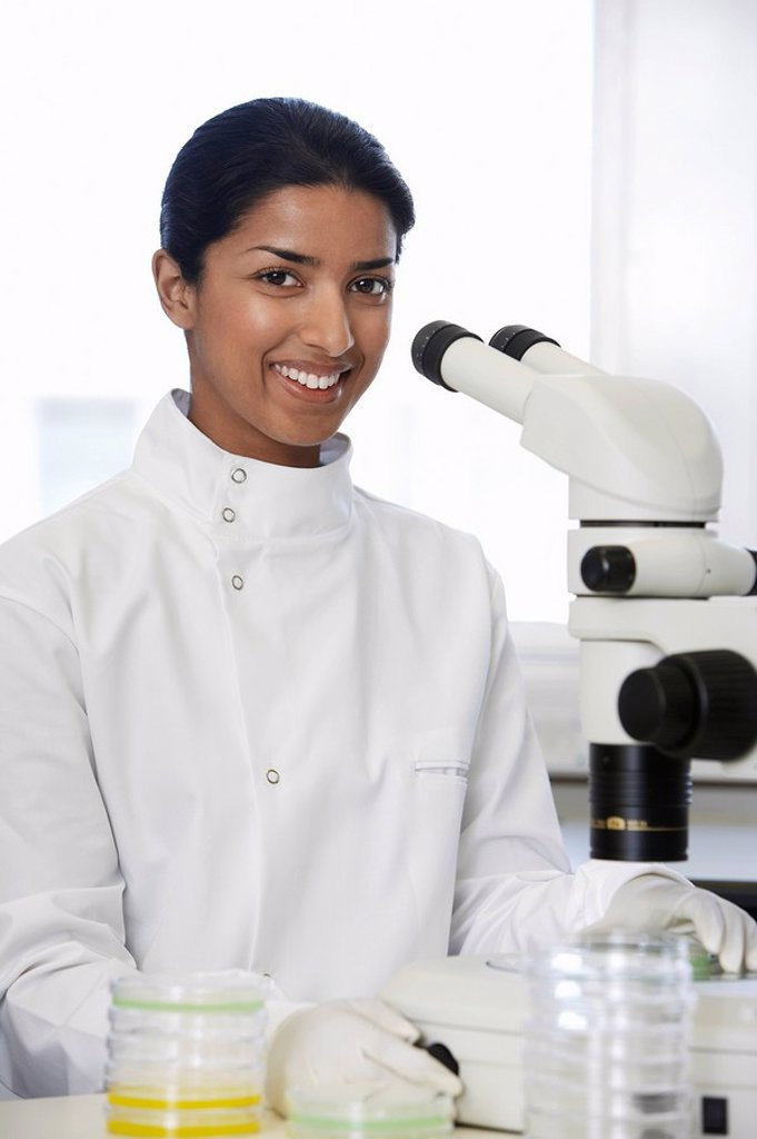 Stock Photo: 1654R-9036 Female Asian lab worker standing by microscope