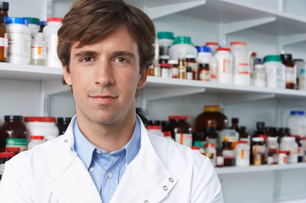 Male lab worker standing pill bottles behind : Stock Photo
