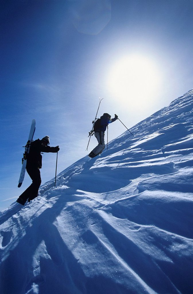 Skiers hiking to mountain summit : Stock Photo