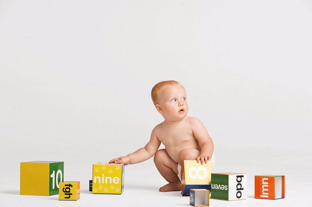 Stock Photo: 1654R-9398 Baby Picking Up Blocks