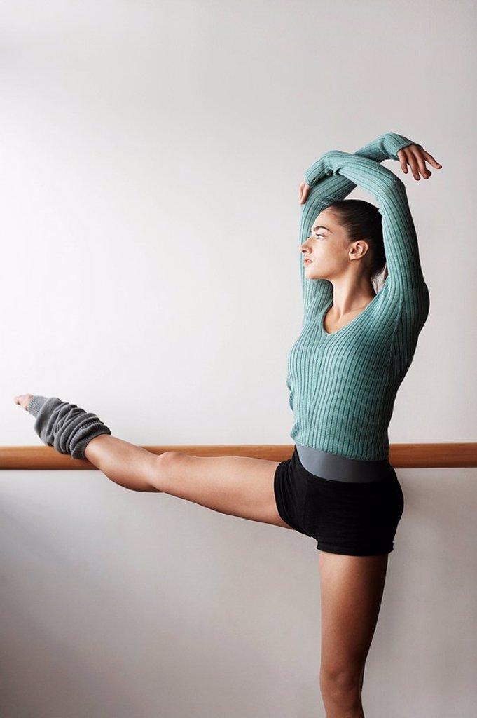 Ballet Dancer Stretching at bar : Stock Photo