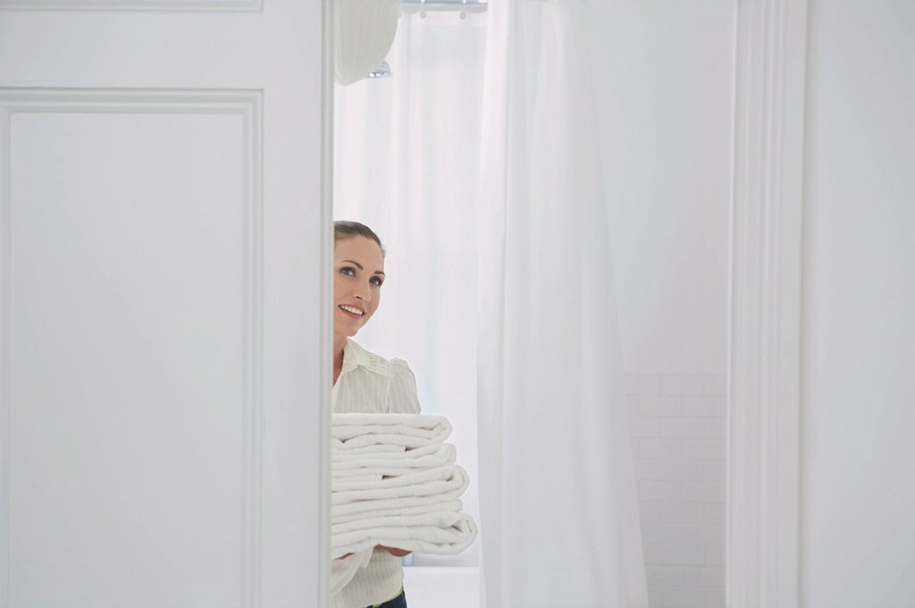 Woman carrying folded linen in home : Stock Photo