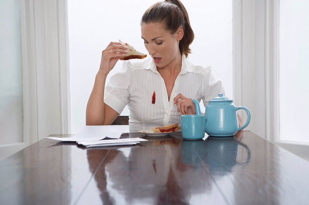 Woman with stain on blouse at dining room table : Stock Photo