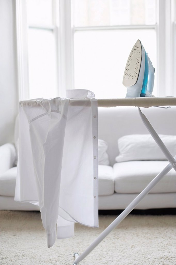White shirt on ironing board in living room : Stock Photo