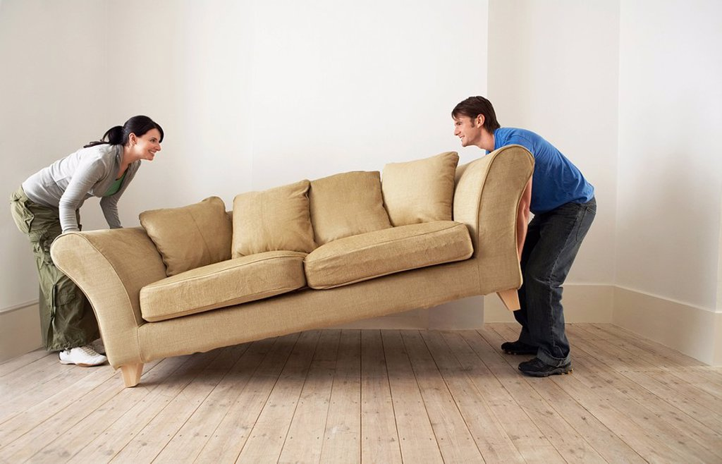 Couple lifting sofa in empty room : Stock Photo