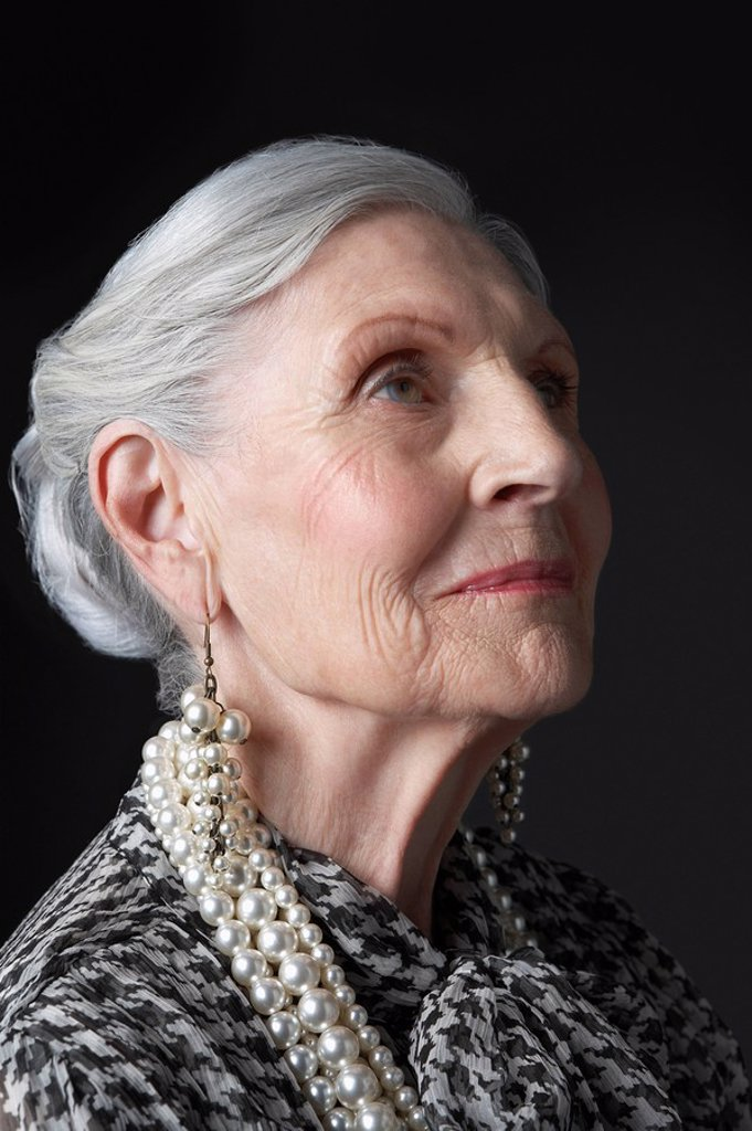 Senior Woman with Pearl Earrings looking up : Stock Photo