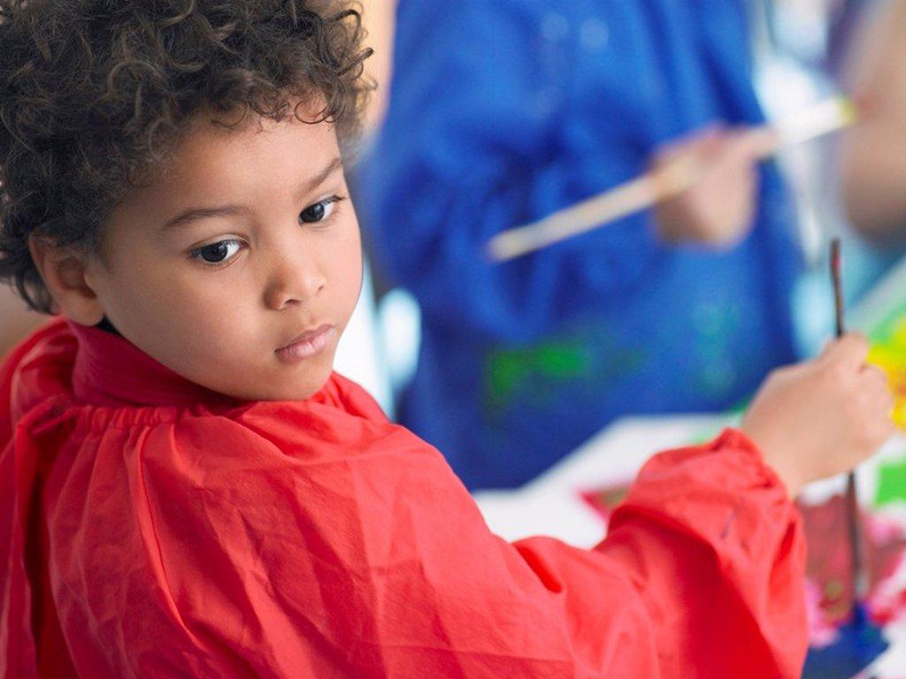 Boy painting in art class : Stock Photo