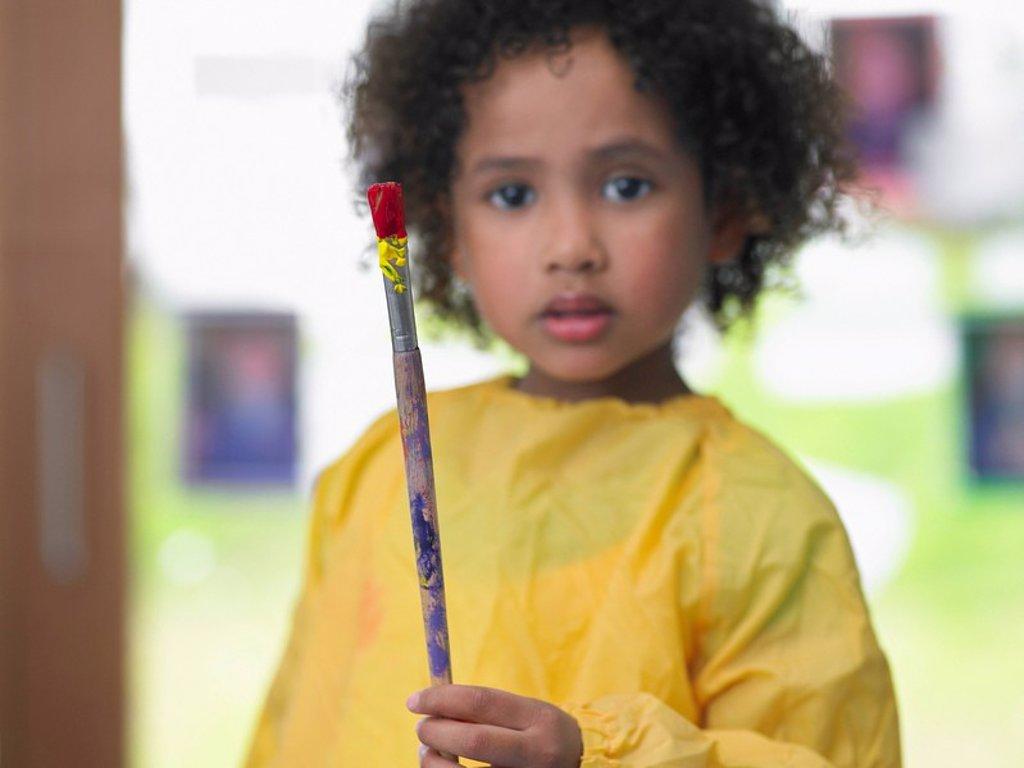 Girl holding paint brush in art class portrait : Stock Photo