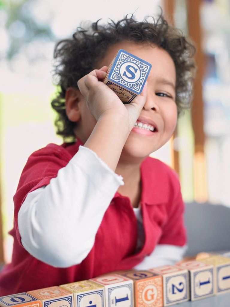 Stock Photo: 1654R-9746 Boy playing with alphabet blocks portrait