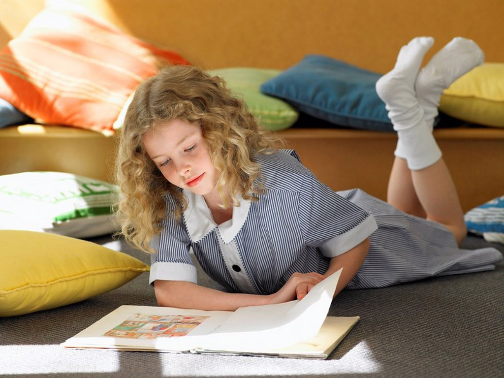 Stock Photo: 1654R-9886 Elementary schoolgirl reading book lying on stomach on floor