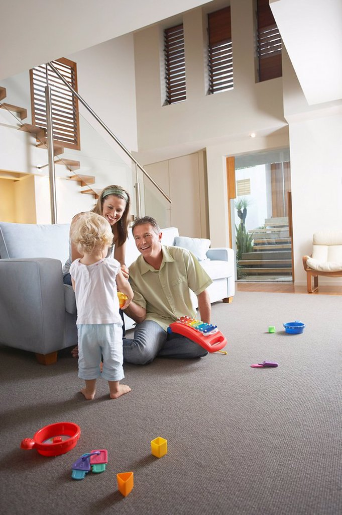 Parents sitting in living room watching son Playing with toys : Stock Photo