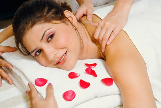 Portrait of a young woman getting a shoulder massage from a massage therapist : Stock Photo