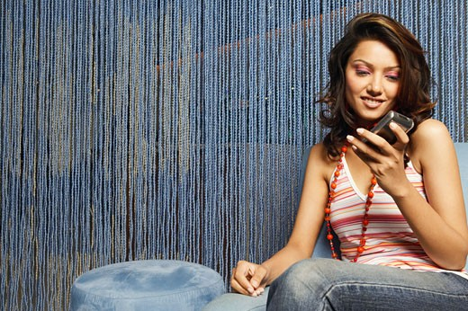Close-up of a young woman looking at a mobile phone : Stock Photo