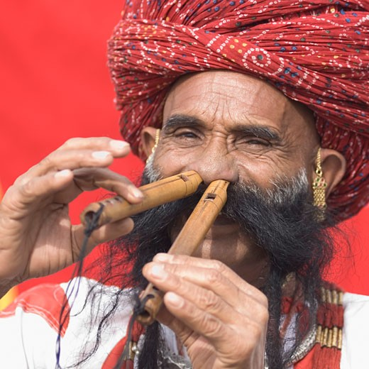 Portrait of a mature man playing flutes with his nose, Jaipur, Rajasthan, India : Stock Photo