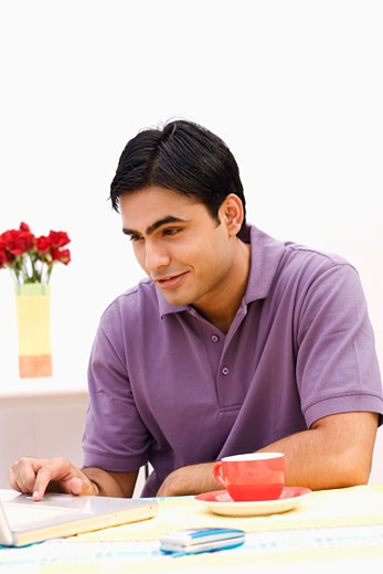 Young man using a laptop : Stock Photo