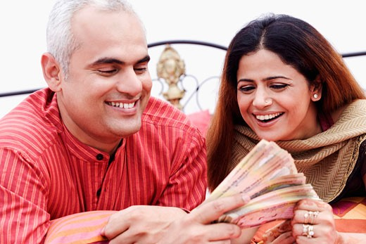 Close-up of a mid adult couple holding Indian currency notes and smiling : Stock Photo