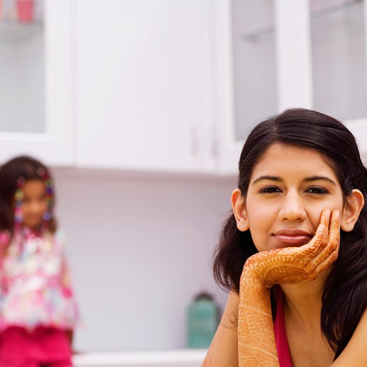 Portrait of a young woman with her hand on her chin with a girl sitting in the background : Stock Photo