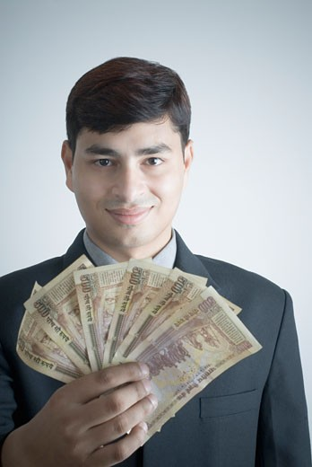 Stock Photo: 1657R-12634 Portrait of a businessman holding Indian five hundred rupee notes
