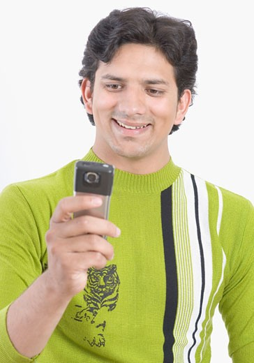 Close-up of a young man using a mobile phone and smiling : Stock Photo