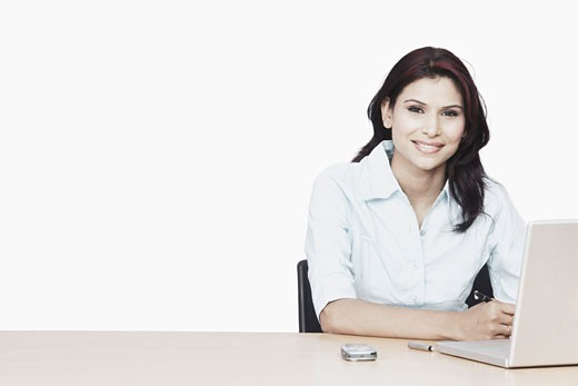 Portrait of a businesswoman smiling in front of a laptop : Stock Photo