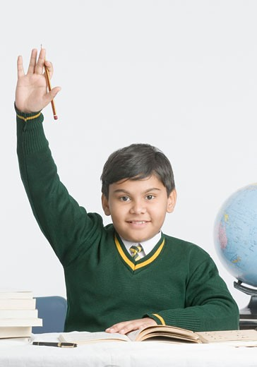 Portrait of a schoolboy smiling with his hand raised : Stock Photo