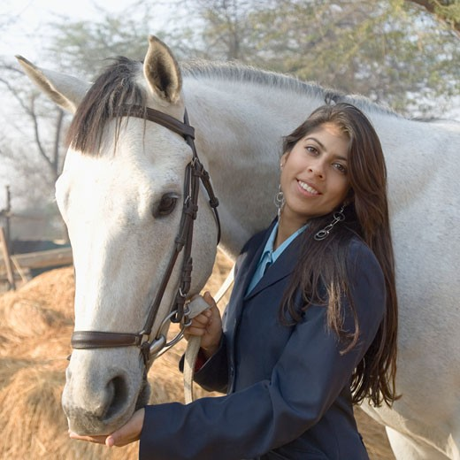 Stock Photo: 1657R-13970 Portrait of a young woman standing with a horse and smiling