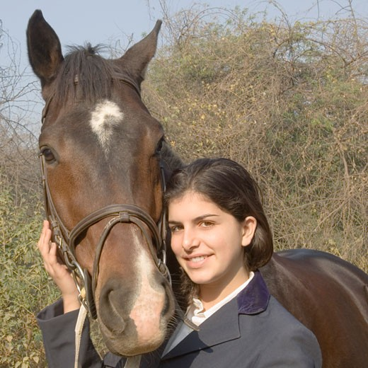 Portrait of a teenage girl standing with a horse and smiling : Stock Photo