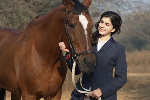 Close-up of a teenage girl standing with a horse and smiling : Stock Photo