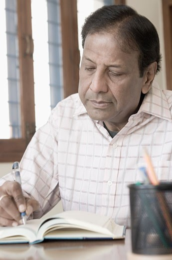 Close-up of a mature man writing in a diary : Stock Photo