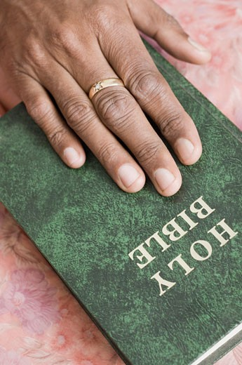 Close-up of a person's hand on the Bible : Stock Photo