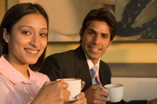 Portrait of a businessman and a businesswoman holding coffee cups and smiling : Stock Photo