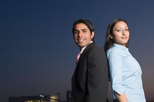 Stock Photo: 1657R-14721 Portrait of a businessman and a businesswoman standing back to back
