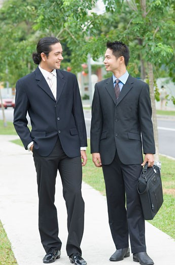 Two businessmen looking at each other and smiling : Stock Photo